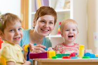 Smiling woman playing with two children in a daycare setting